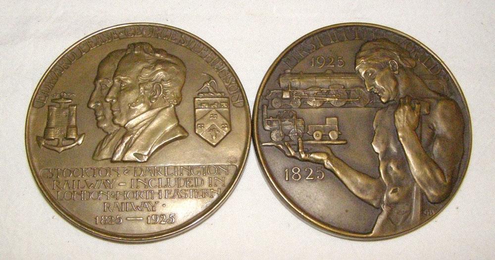 """Minnesmynt av brons. På framsidan av myntet avbildas en arbetare med bar överkropp som håller i ett miniatyrlok. På baksidan ses två personer i profil med deras vapen. Text på framsidan: """"First in the world 1825 - 1925"""". Text på baksidan: """"Edward Pease. Georg Stephenson. Stockton & Darlington rail- way - included in London & North Eastern railway. 1825-1925"""".  Se även Jvm12223."""
