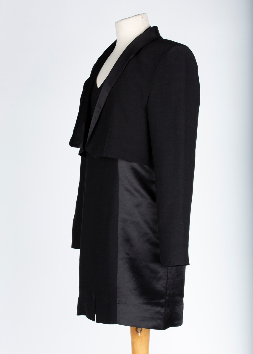 Kjole med jakke.  A: kjole: Kort , ettersittende kjole. Nakkestropp lukkes med to trukne knapper. Åpen rygg. Glidelås i ryggen. 8 bredder. Buet brystsnitt. Kort splitt i sidene. Spiss halsringing forran. Kjolestoffet har en blank og en matt side , brukes effektfullt sånn at breddene midt forran og bak vender den matte siden ut, den blake siden vises i sidene og på halsstroppen. Kjolen er helforet med sort forstoff  B: Jakke. Bolerojakke, Åpen forran, sjalskrage i blankt stoff. lange armer. skulderputer. Lengdesnitt  på forstykkene. Helforet. Meget god tilstand Kjolen brukt i Follo og i Oslo1985/86 - oppludt fra giver