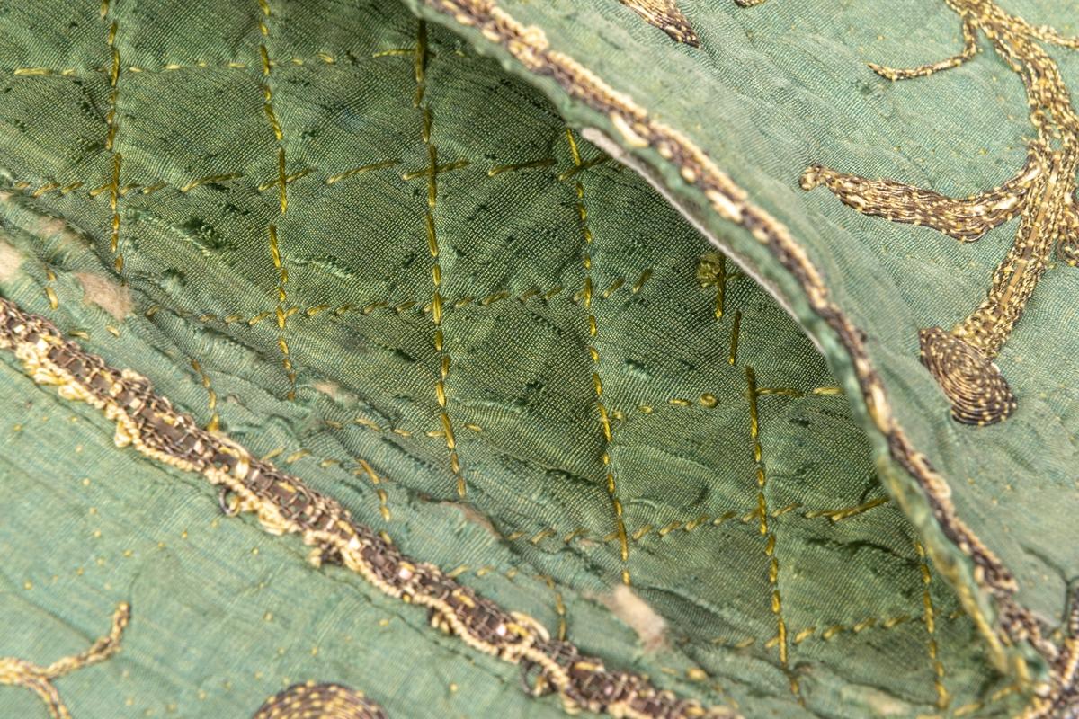 Plånbok av grönt siden med guldbroderi, vadderad och stickad i rutor.