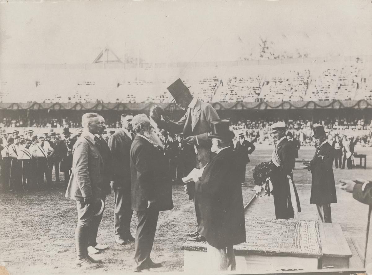 Grupp M V.  Skytten Oscar Gomer Swan tilldelas medalj av kung Gustav V under Olympiska spelen i Stockholm 1912 för segern i löpande hjort enkelskott, lag. Guldmedaljen från 1912 som Oscar Swahn vann vid en ålder av 64 år och 257 dagar gör honom till tidernas äldste olympiske guldmedaljör.
