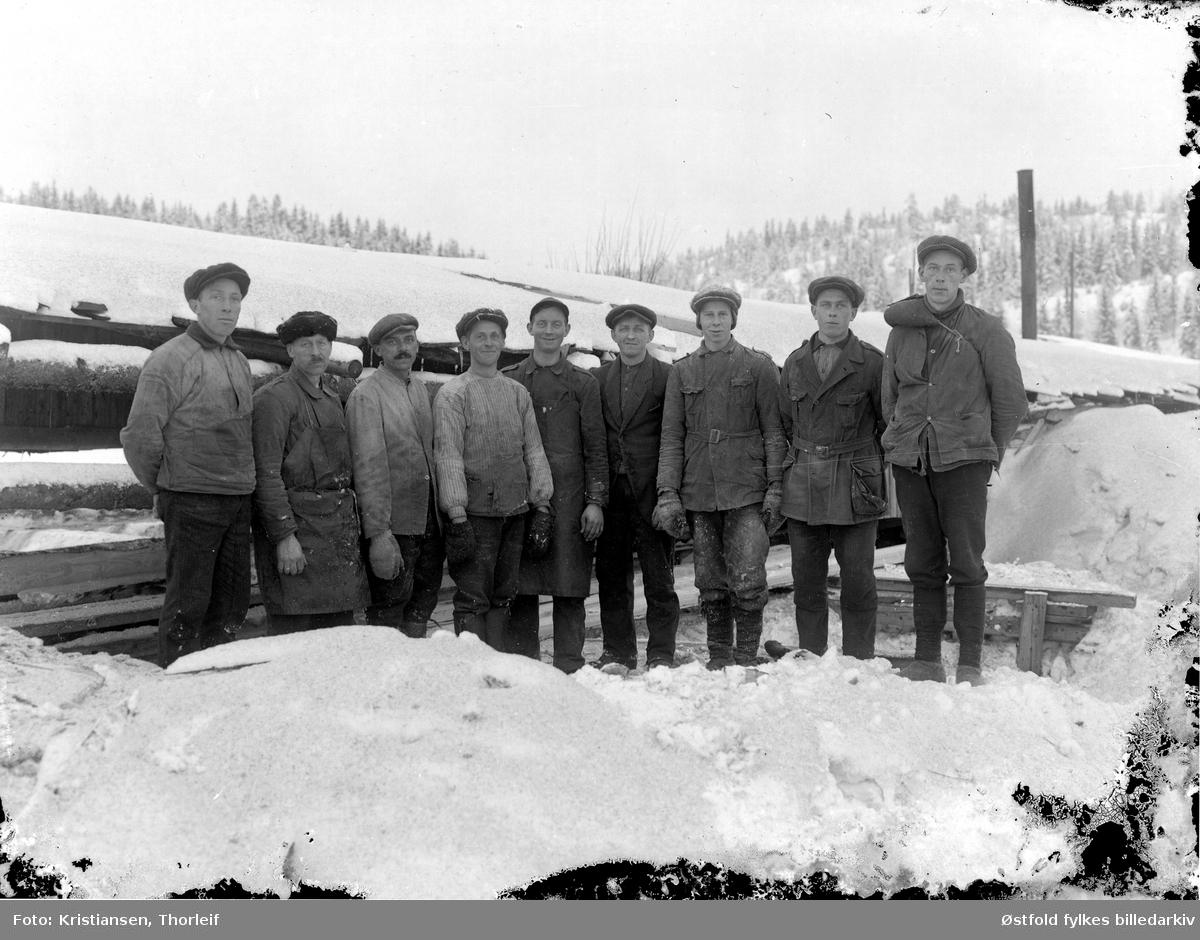 Arbeidsmannskap, gruppeportrett av mann i arbeidsklær, vinter og snø, ukjent. sted.