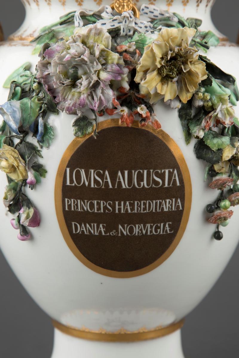 Plastisk flerfarget blomsterdekor med sløyfer øverst på begge sidene av korpus. På den ene siden under blomsterdekoren finner vi en medaljong med forgylt rand og påskriften «Lovisa Augusta Princeps Hæreditaria Daniæ & Norvegiæ.» På foten under medaljongen malt i grisaille en blomsterkrans med sløyfe og trepinne. På motsatt side av vasen en medaljong med forgylt rang og et grisailleportrett av prinsesse Lovisa Augusta. Portrettet er malt etter forelegg av Johan Frederik Clemens stikk av Louisa Augusta fra 1785. På foten under medaljongen malt i grisaille en laurbærkrans med harpe og stearinlys. På hver side under hankene malt i grisaille overflødighetshorn og blomsterkranser. På lokket en Putto med vinranker. På fremsiden av lokket malt i grisaille Danmarks riksvåpen. På baksiden malt i grisaille et innrammet motiv av soloppgang og jorden omsluttet av bladranker og Ouroboros (slange som biter seg selv i halen).  Forgylt dekor med rocailler langs foten og munningsdelen. Øverst på korpus et dekorbånd med medaljonger og girlander. Hankene er formet som grener med blomster.