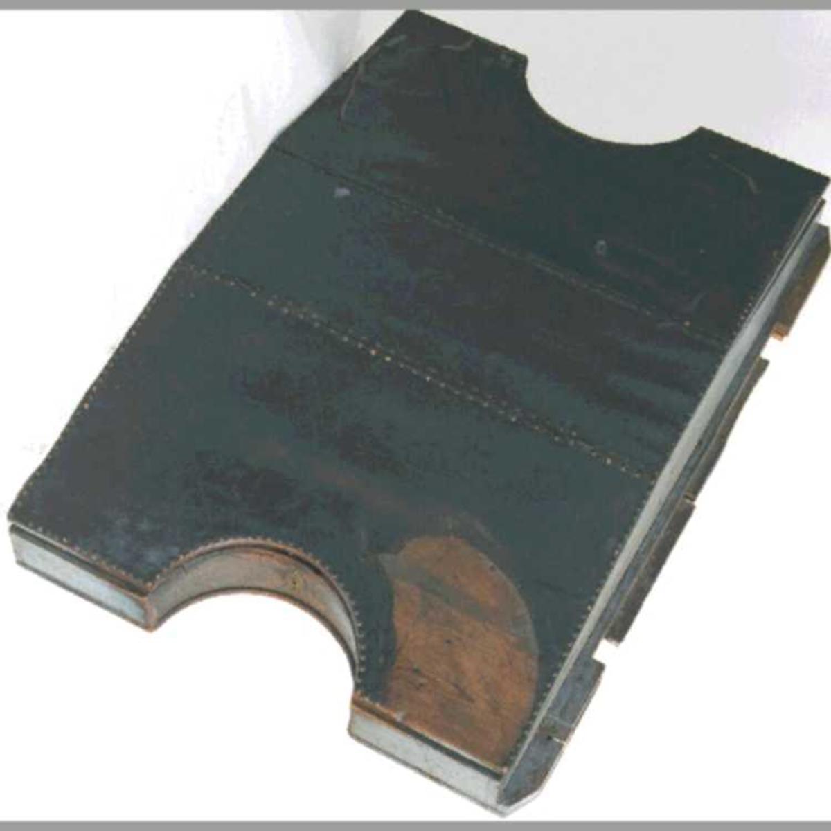 Furu  , malt lyst gråblå, platen trukket med   okselær,  stiftet langs kantene med   messing  stift med runde  hoder. Pulten er dobbel, slik at to skrivere  sitter på hver sin side av den mot hverandre. Pulten  har utskårne halvsirkelrundinger ved plassene.  Står på ramme av rette ben, med rette forbindelseslister  oppe og nede. Pultplatene er til å løfte opp  som lokk, med låser. Lås mangler, nøkkelskiltet av messing  bevart på den ene plass. Hele trestykket  som låsen har sittet på, forsvunnet fra den andre.  Pulten skråner til begge sider, og har flatt  topp stykke