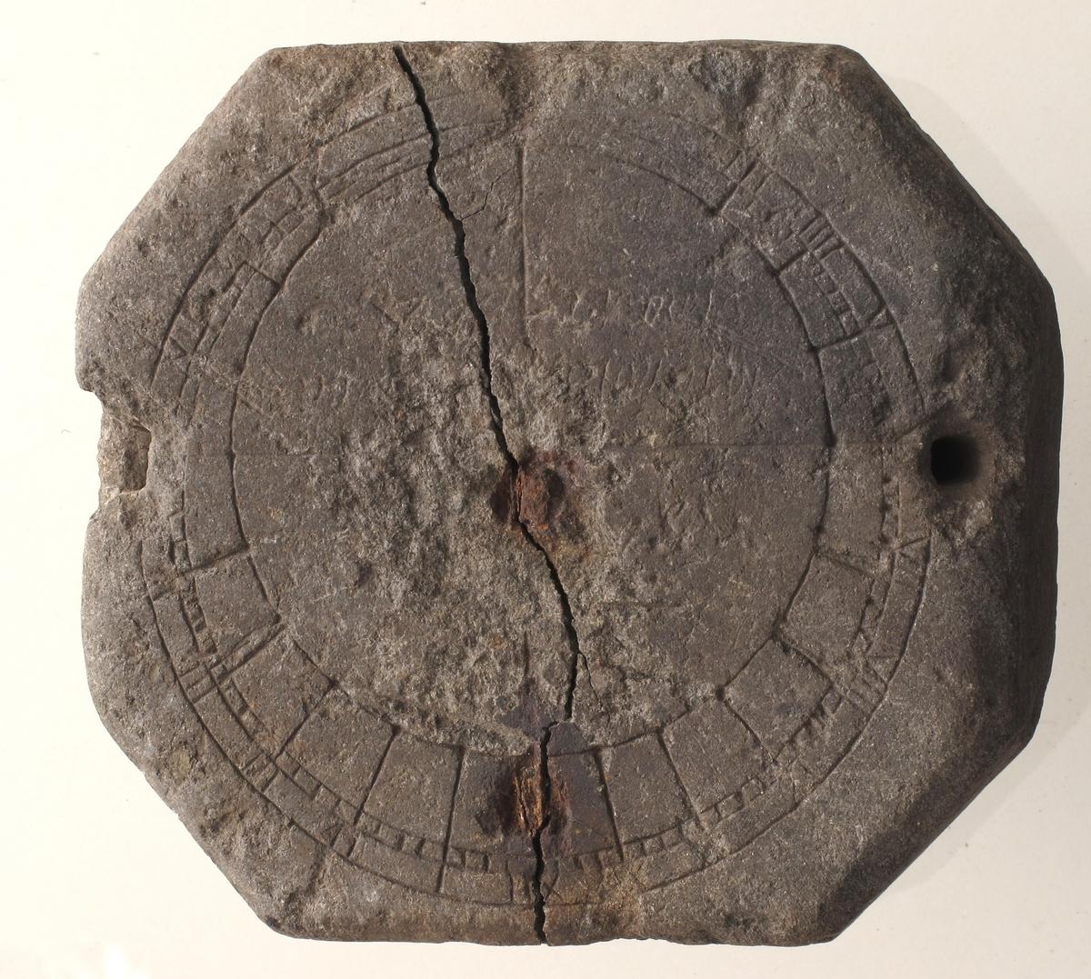 Tykk, flat 8-kantet sten med et inndelt sirkelbånd innskåret langs kanten, avslitt særlig i hyre halvdel. Et gjennomgående hull oppe og nede.   tilstand: Stor sprekk tvers over midten, to rustne jernnagler som er sat på til forstekning. Ståltråd festet i øvre hull.