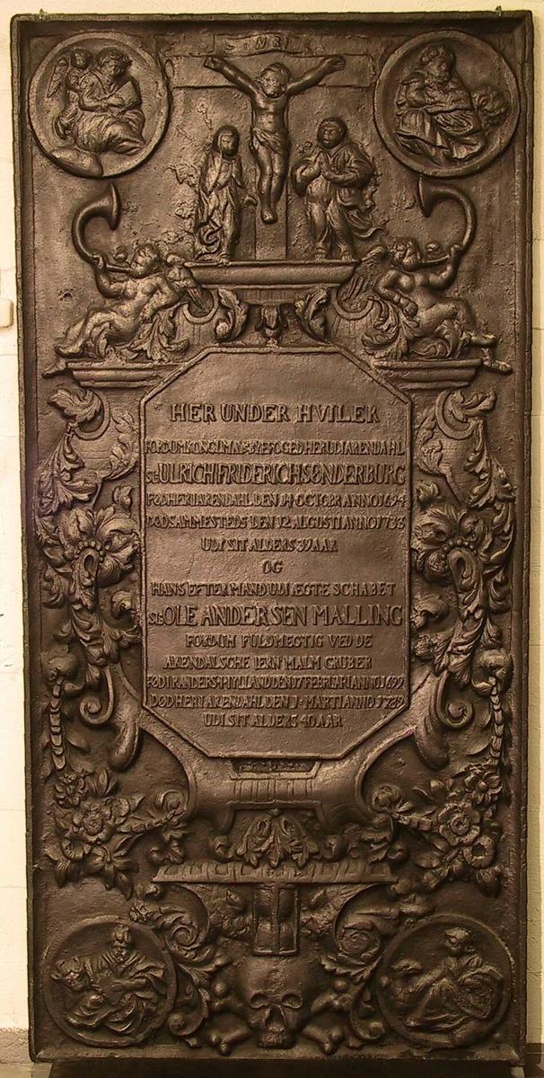 Relieffdekor./ korsfestelsesfremstilling,/ evangelistene med symbol  Korsfestelsen,  i hjørnene   evangelistene med symboler i sirkulære  medaljonger.  Under disse øverst   to basunspillende engler,  langs siden av teksten  svulmende ranker med blomster.  Under tekstfeltet pm. et   timeglass og et kranium.