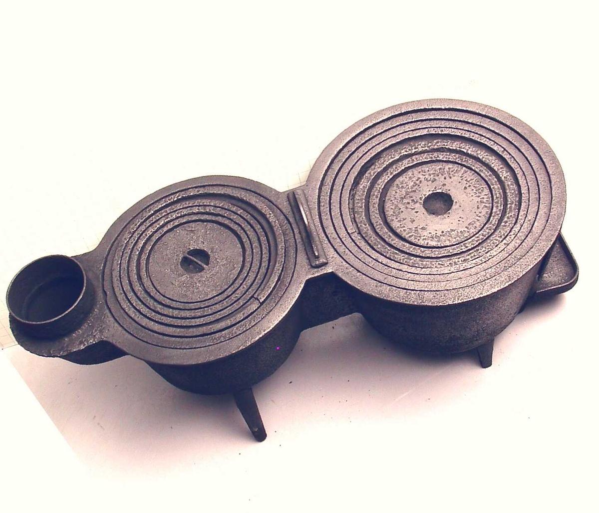 Kokeovn. dobbelt grytehull, på fiolinformet ovnsplate.  Støpejern.  Stemplet på ileggsdør.  2 kokegryter bak hverandre.  gryteformen tydelig. den største foran.  4  ben.  Trekkregulator med handtak mellom de to gryter.