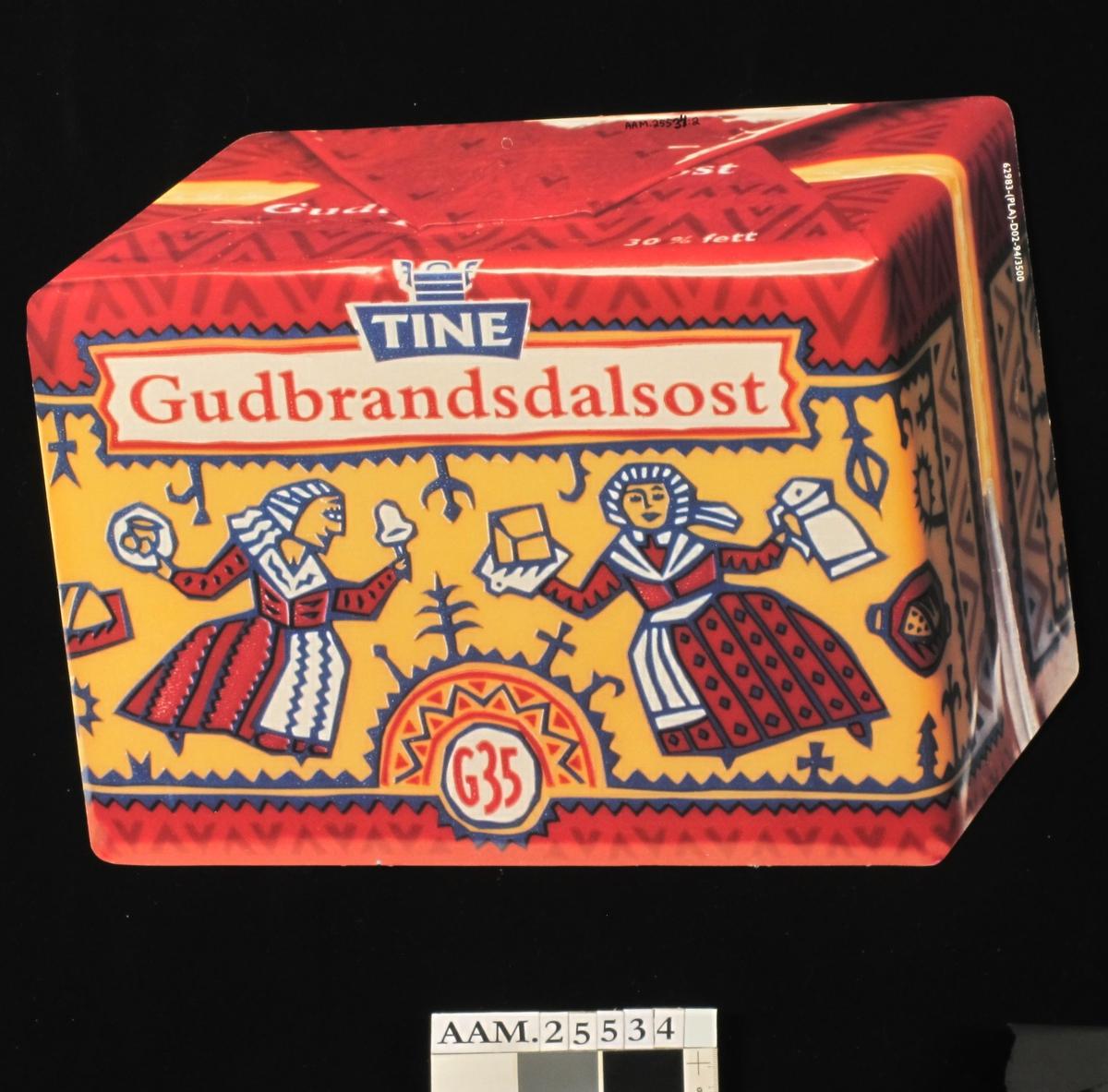 Fargefoto av fløtemysost i plastinnpakning. Osten er pakket i plast, dekorert med tegnet motiv: To budeier med ostestykker, ostehøvel m.m. innrammet i primstavmotiv.