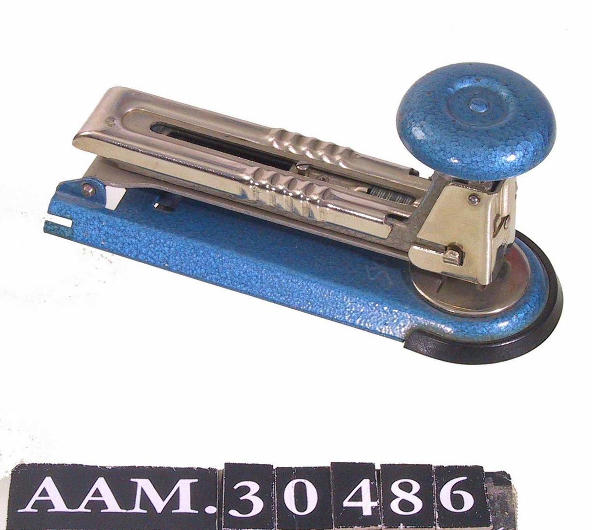 Form: Buet plate i bunnen. Avlang maskin festet i den ene enden, kan vippes opp på den andre, hvor selve stiftemekanismen er et skålformet håndtak med fjæring.