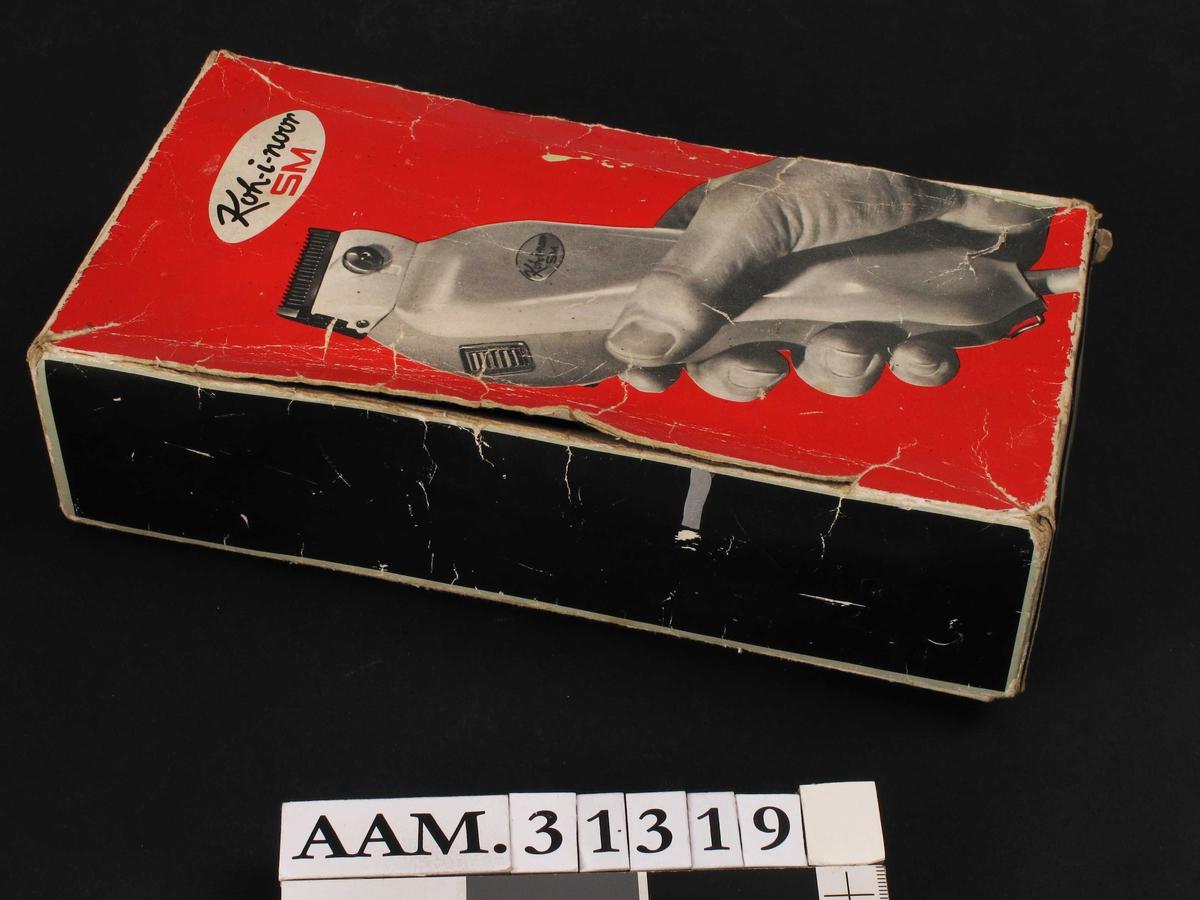En hånd som holder en elektrisk klippemaskin (på eske).
