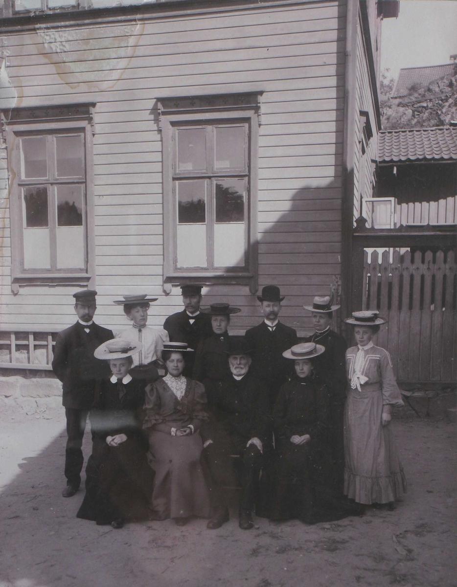 Fotografi tatt utendørs foran skolebygning, av en gruppe lærere, 4 menn og 7 kvinner. Kvinnene er ikledd fantastiske hatter.
