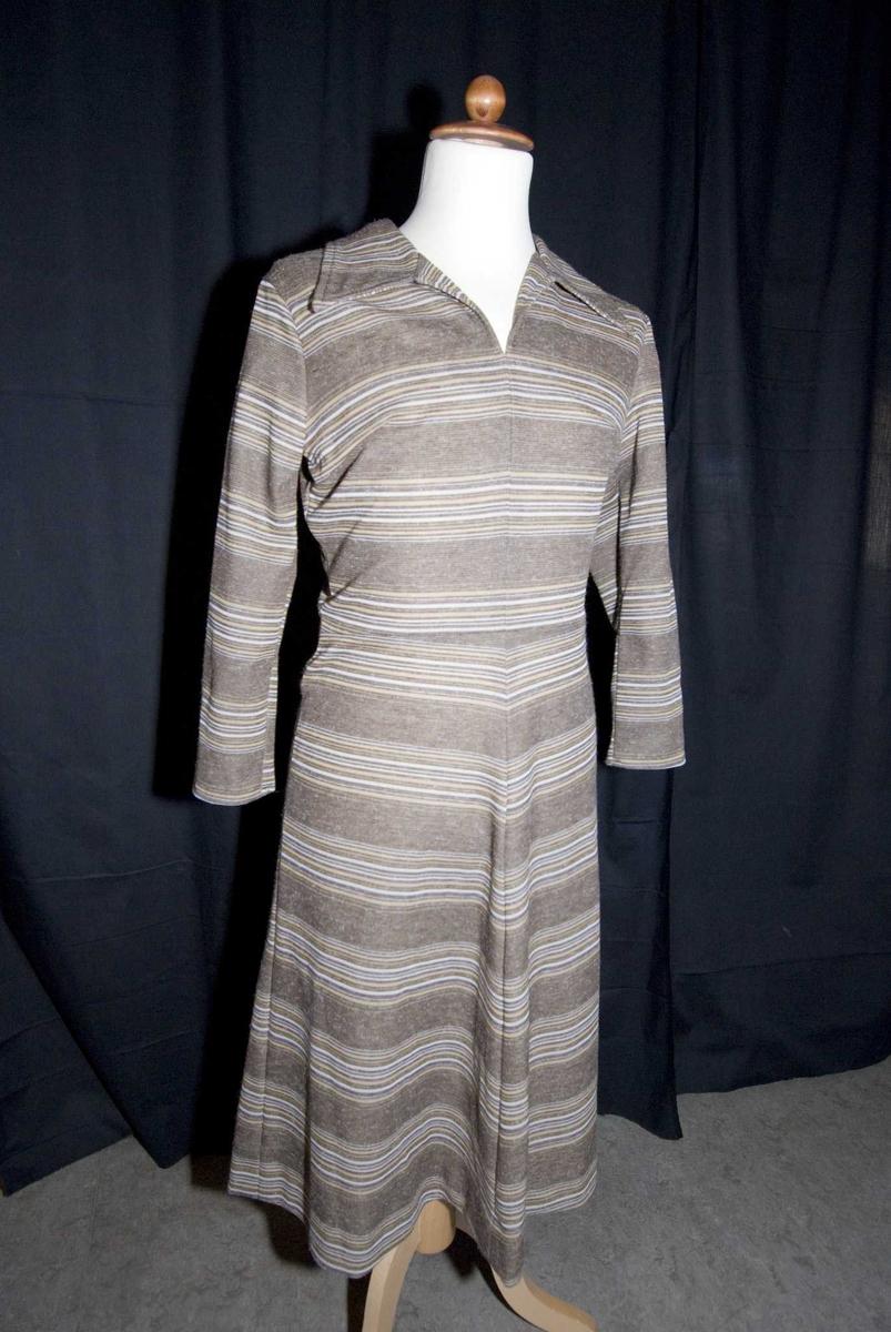 Brunstripet kjole med lange ermer og krave og V-hals, lukket med glidelås i ryggen. Skrådd skjørt i 4 bredder. Preserver i ermene. Hjemmesydd.