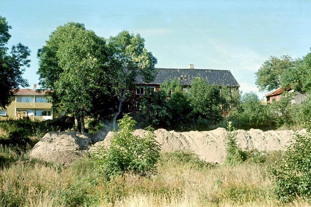 Nedeneshus. Saltrød gård. Rødmalt husvegg, hage og trær. Oppgravd grøft. Fotografert før riving.