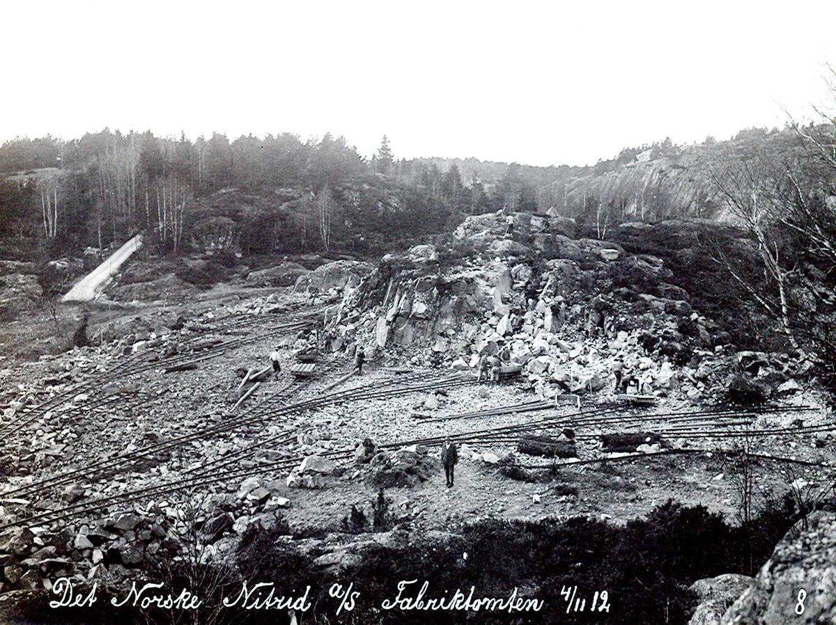 """""""04/11-1912"""" Nitriden. Fabrikktomten. Fjell sprenges bort. Minering med handmakt. Skinneganger og traller for bortkjøring av steinmassene som fylles i sjøen. Vei til anleggene til venstre. På høyden til høyre ble bygd høydebasseng for trykkvann til bedriftene."""