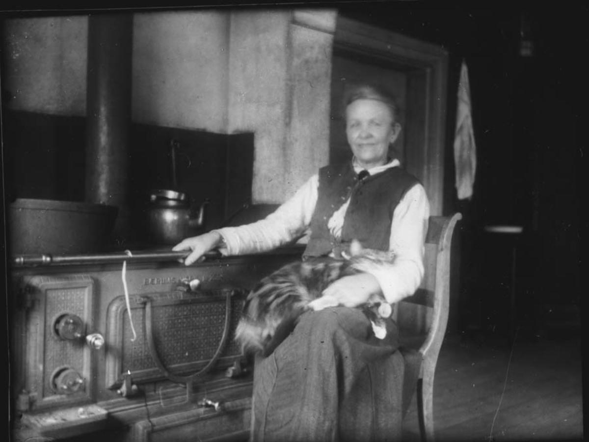 Fredrikke Østby på kjøkkenet ved jernkomfyren