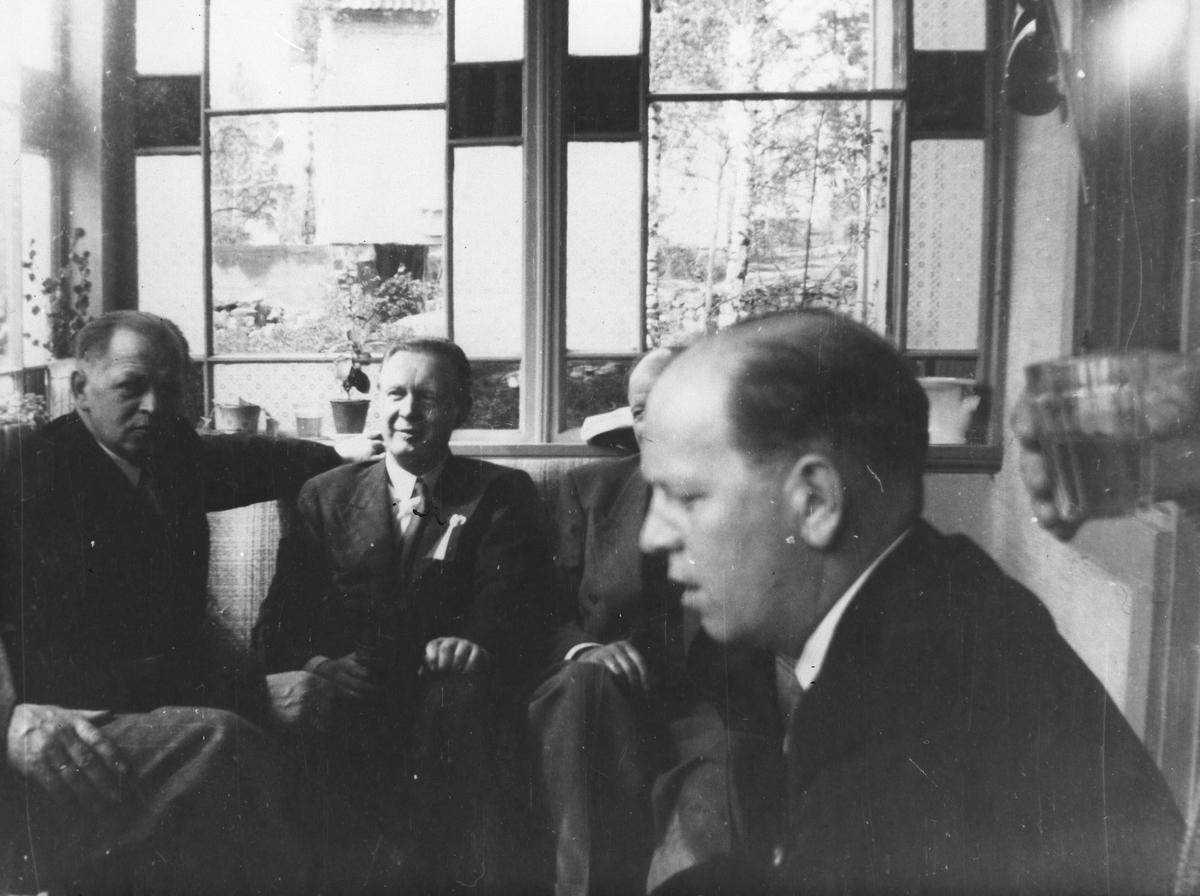 Fire menn på kafeveranda.