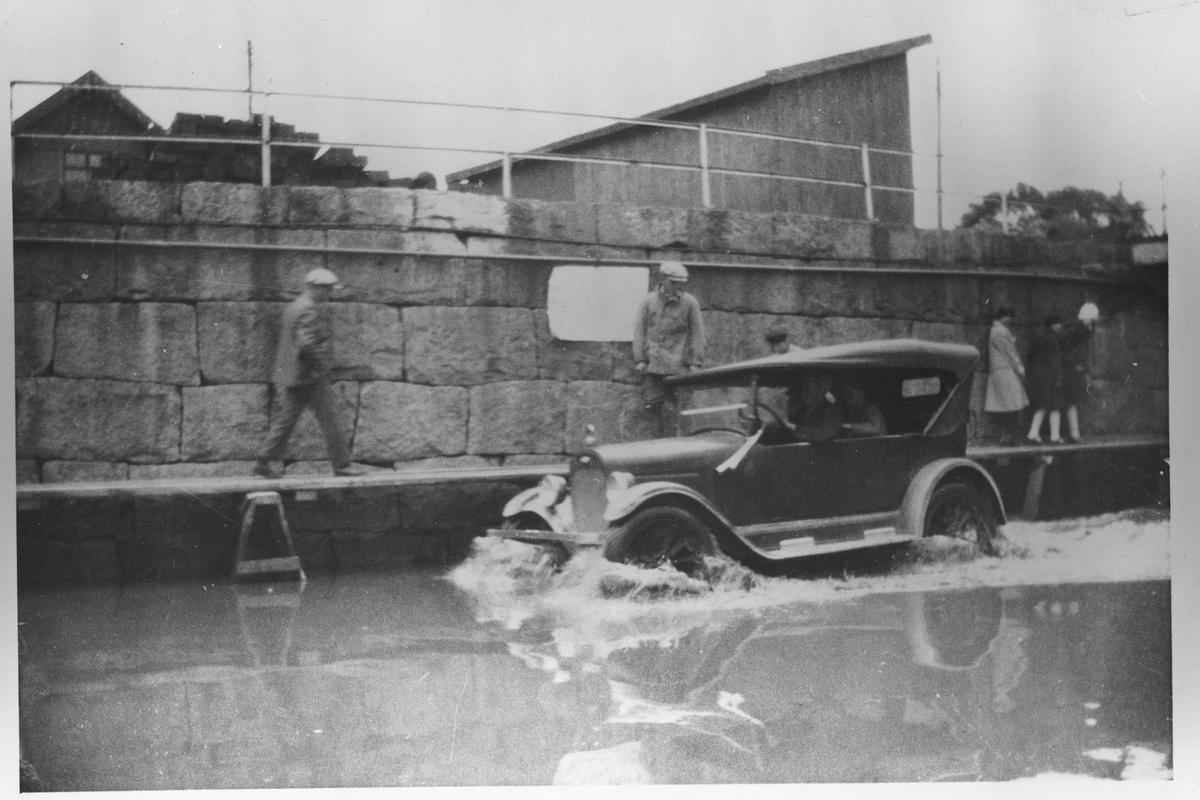 Fra flommen i 1927. Bil og personer i oversvømmet gate.