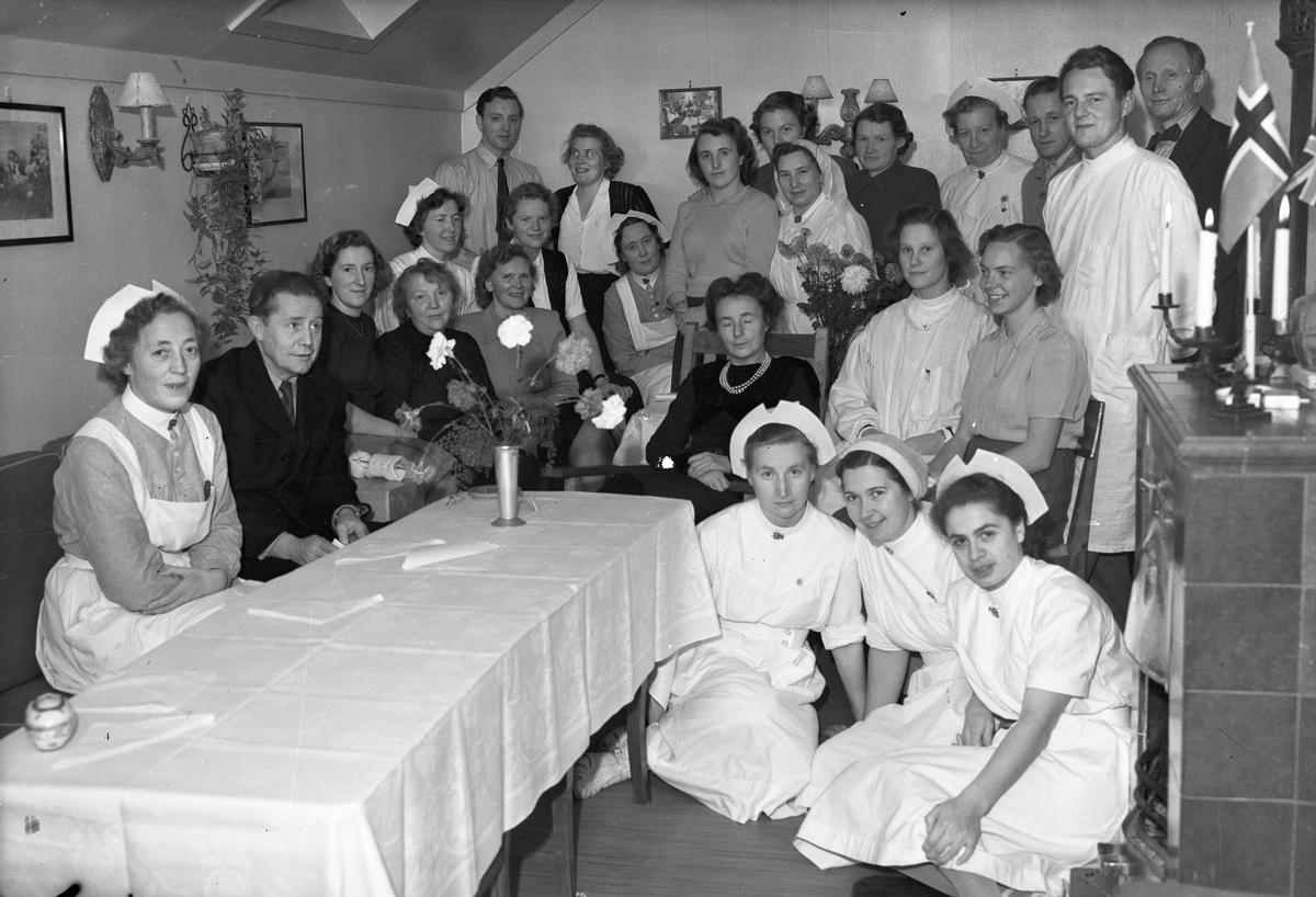 Personale i hvite uniformer. På kvinnenes uniformer har de merket til NKS – Norske Kvinners Sanitetsforening.