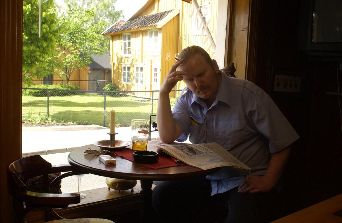 Pubgjest med røyk, øl og avis ved vinduet Milde Moses Pub & Spiseri i Drøbak