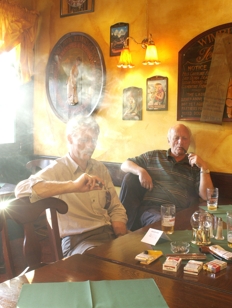 2 menn ved et bord med sigarer og pipe. Bowler & Spisepub.