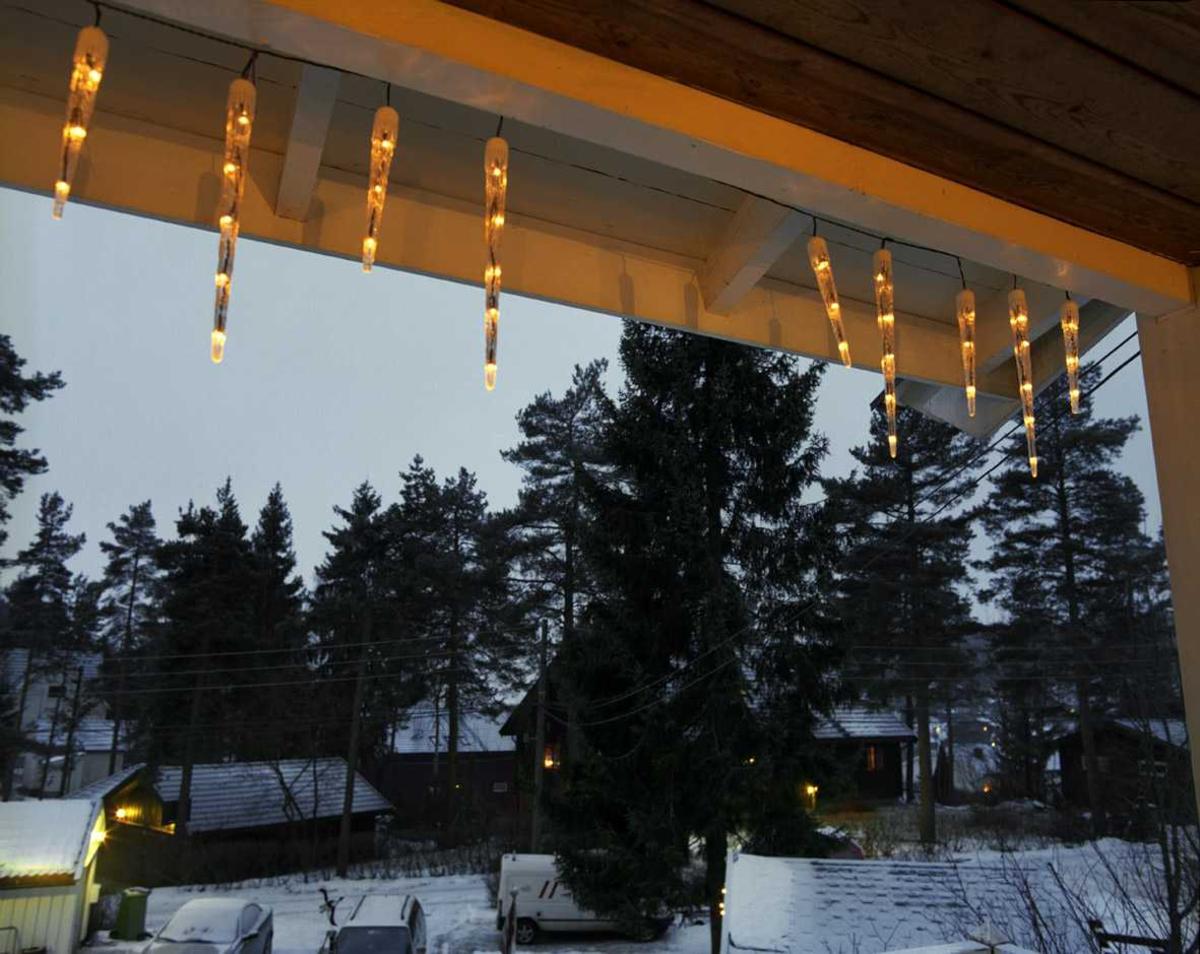 Julebelysning  Lysende istapper på veranda ved enebolig