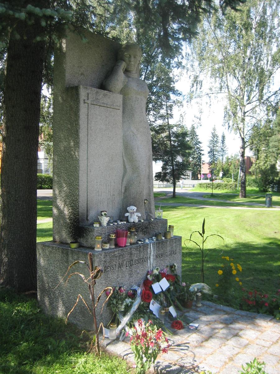 Minner etter terrorhandlingen den 22. juli 2011. Blomster, kort og lykter ved Krigsmonument ved Lillestrøm kirke.