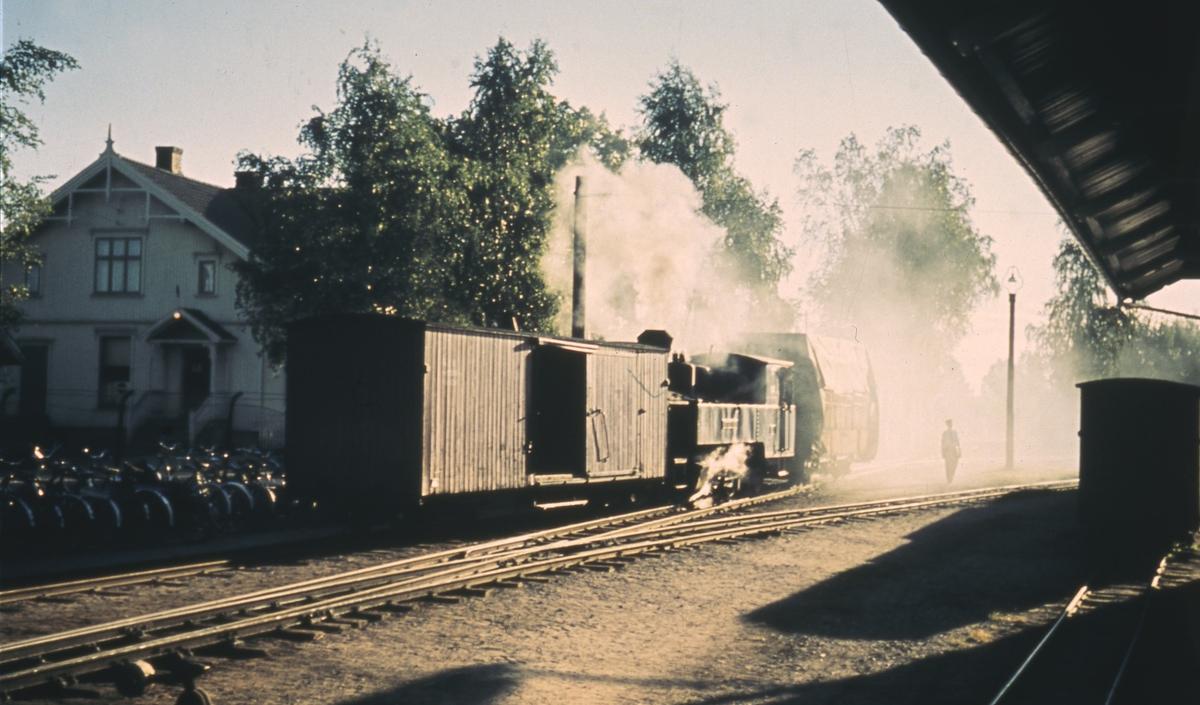 Skifting på Sørumsand stasjon. Fullastet vogn med torvstrøballer bak lokomotivet.