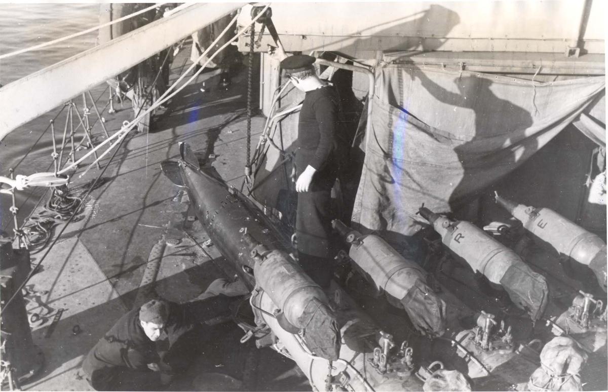 """Enkeltbilde. Jageren """"Stord"""" under oppøving, klarsjøing. En torpedo blir tatt ut av en av rørene for å bli sett over mens skipet ligger til land i Scapa Flow."""