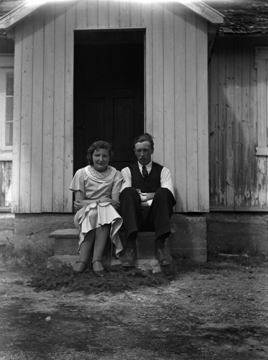 Ukjent jente og gutt på trappa ved inngangen til et hus.