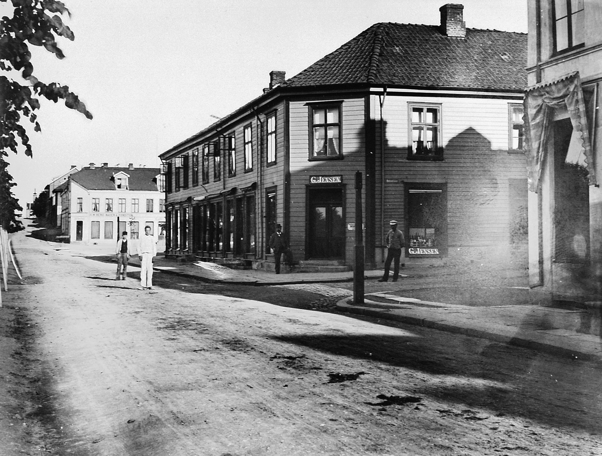 "Simensgården. G. Jensen Kolonialforretning i Strandgata, Hamar. Satt opp i 1850, gården brant ned i 1946. I dag ligger ""Casa Blanca"" her."