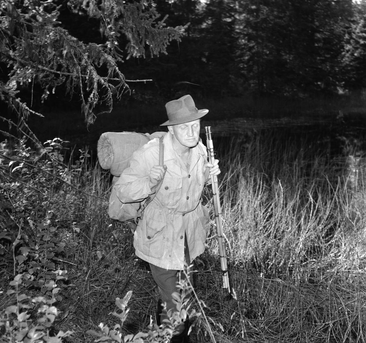 Guttorm P. Haugen. (f. 1911-d. ) Portrett, med sekk og fiskestang. Friluftsliv.  kunstner; visedikter, forfatter og maler.