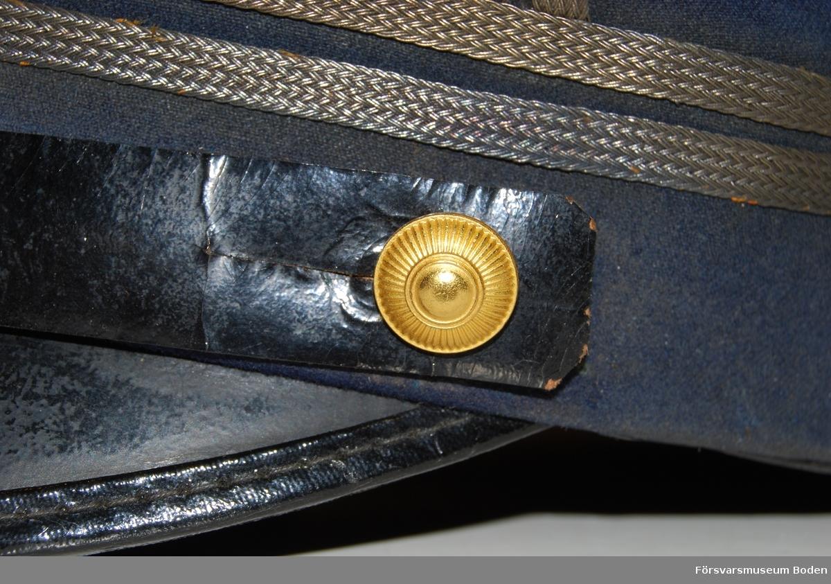 Mörkblått kläde med skärm och hakrem av svartlackerat läder. Hakremmen fastsatt på sidorna med artilleriets knappar modell mindre i guld. Två smala silvergaloner runt mössan, betecknande löjtnant.  Framtill mössmärke för officerare i blå emalj och ovanför denna en gul sidenkokard.