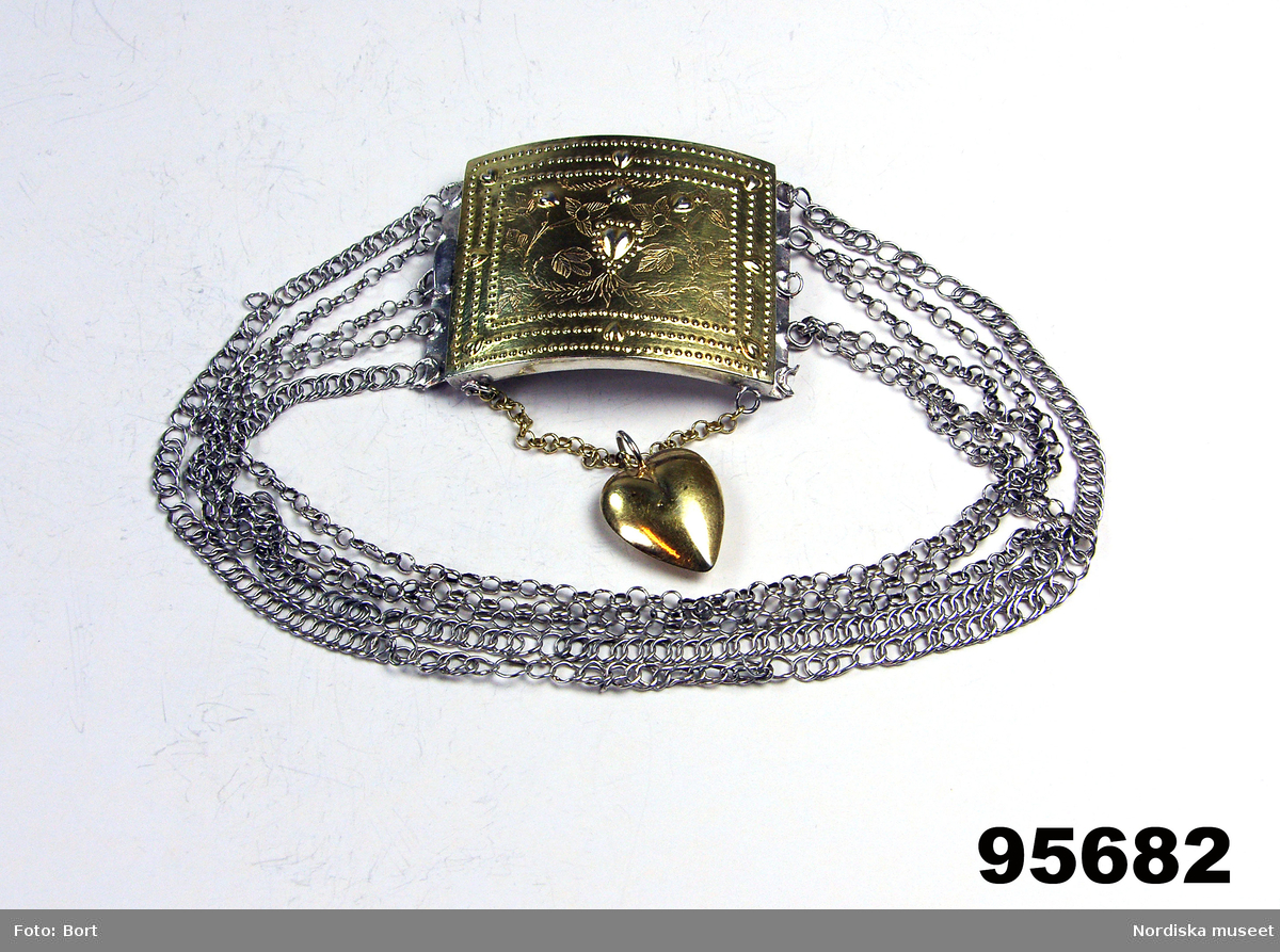 """Huvudliggaren: """"Halslås. Av silver. Själva låset och 1 hjärtformigt hänge förgyllt. 5 halskedjor. Fr. 1829 (Y3)  Halslås av rektangulär något buktig silverplåt med pressad dekor i form av små hjärtan och prickrader samt graverade bladrankor. Under låset en kort ankarkedja med ett hängande förgyllt hjärta, runt halsen 5 kedjor; 2 pansarkedjor och 3 ankarkedjor. Stämplat av Gustaf Wilhelm Nordström i Växjö 1829. /Berit Eldvik 2006-12-17"""