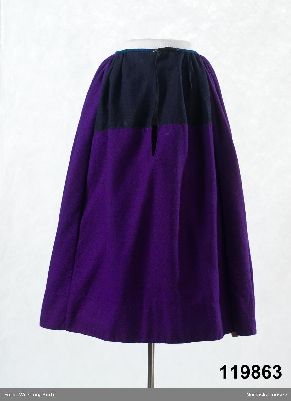 Kjol av starkt anilinlila halvylle, varp av ljusbrunt bomullsgarn, inslag av lila entrådigt ullgarn. 5 våder, framvåden har iskarvade bitar av svart kjoltyg i halvylle vid mittsprundet fram,  stripade och knäppta  rynkor runtom  midjan utom en decimeter vid sidorna om sprundet som är slätt . Linning av mörkblått halvylle, skoning av  12 cm brun  bomullslärft, s.k. domestik. Handsydd med vit lintråd . Arnbergs Färgeri i Floda försåg hela Västerdalarna med färgning. 1873 var första gången de färgade med den nya anilinfärgen violette, som sedan blev så vanlig i dessa trakter. De kjolar som tidigare varit blå, blev nu starkt anilinlila. De fick fortsatt benämningen blåkjortel.  Se blå kjol inv.nr 197 476. Läs mer om dräktskicket i Floda i: Albert Alm, Dräktalmanacka för Floda socken, Nordiska museet, Sthlm 1930. /Berit Eldvik 2011-10-27