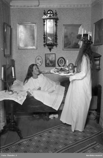 Luciamorgon. Lucia med ljuskrona och kaffebricka lussar för flicka i säng. Filipstad, Värmland.