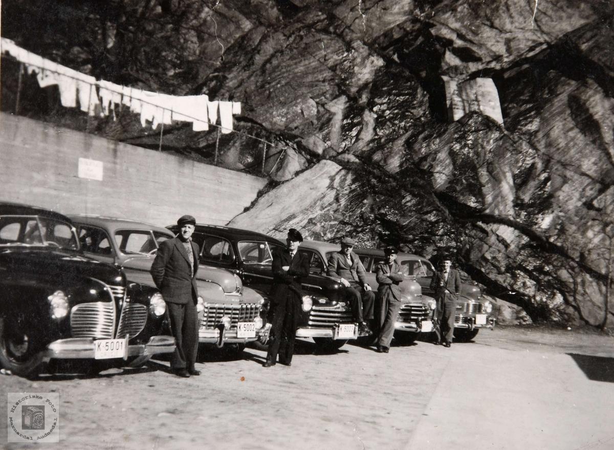 Drosjeparken i Mandal på 1950 tallet. Drosjene fra venstre: K-5001 Plymouth 1940, K-5002 Dodge 1946-48, K-5003 Ford 1946, Chevrolet 1947, Nash 1946-48.  Brukerkommentar september 2020: Til venstre: Rolf Morris Jahnsen.