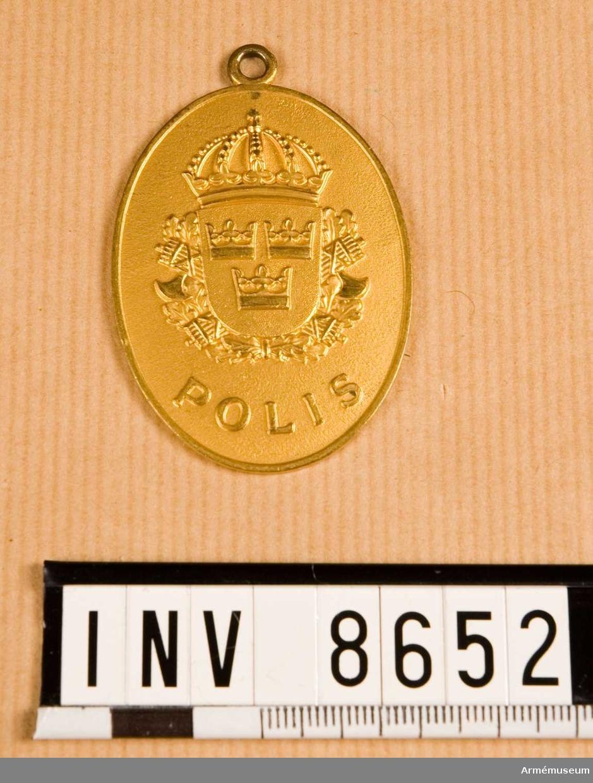 """Höjd 55 mm. Bredd 40 mm. Vikt 29,2 g. Förgyllt ovalt märke med det lilla riksvapnet vilande på ekkvistar och två korslagda fasciner. Utmed den nedre kanten står det """"POLIS"""". Frånsidan är märkt """"KRIGSPOLISEN MARINEN 49"""". Märket har upptill en ring."""