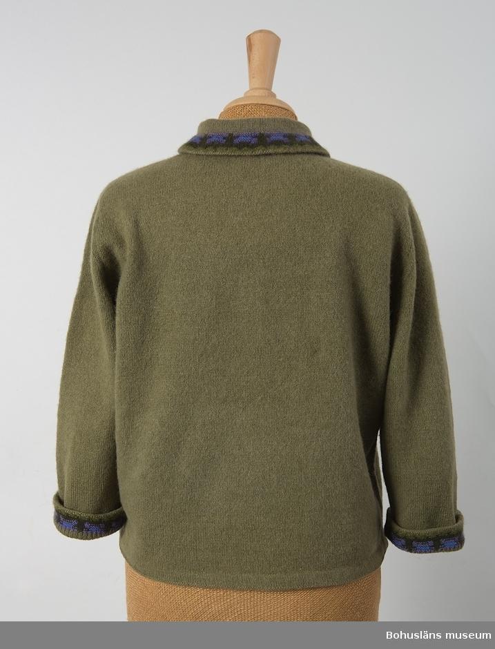 Jumper, finull-/angoragarn, gröngrå botten med mönsterstickad bård runt halskragen, en s.k. skorstenskrage samt runt uppvikt ärmavslutning (4 cm uppvik). Bårderna går i mörkare grönt, lila och blått. Originaletikett: Bohus Stickning