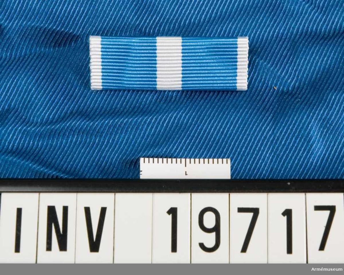 Blått band med vita kanter och en vit rand i mitten. Fastsydd säkerhetsnål. Släpspännet förvaras i ask tillsammans med en miniatyrmedalj och en medalj.