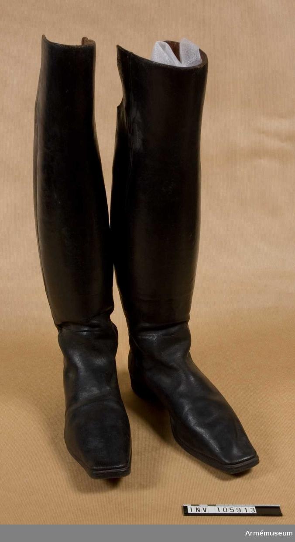 Grupp C I. Kragstövlar för officer. Av svart läder, raka, med stor utskärning på baksidan, för knäveck. Smala stövelspetsar.