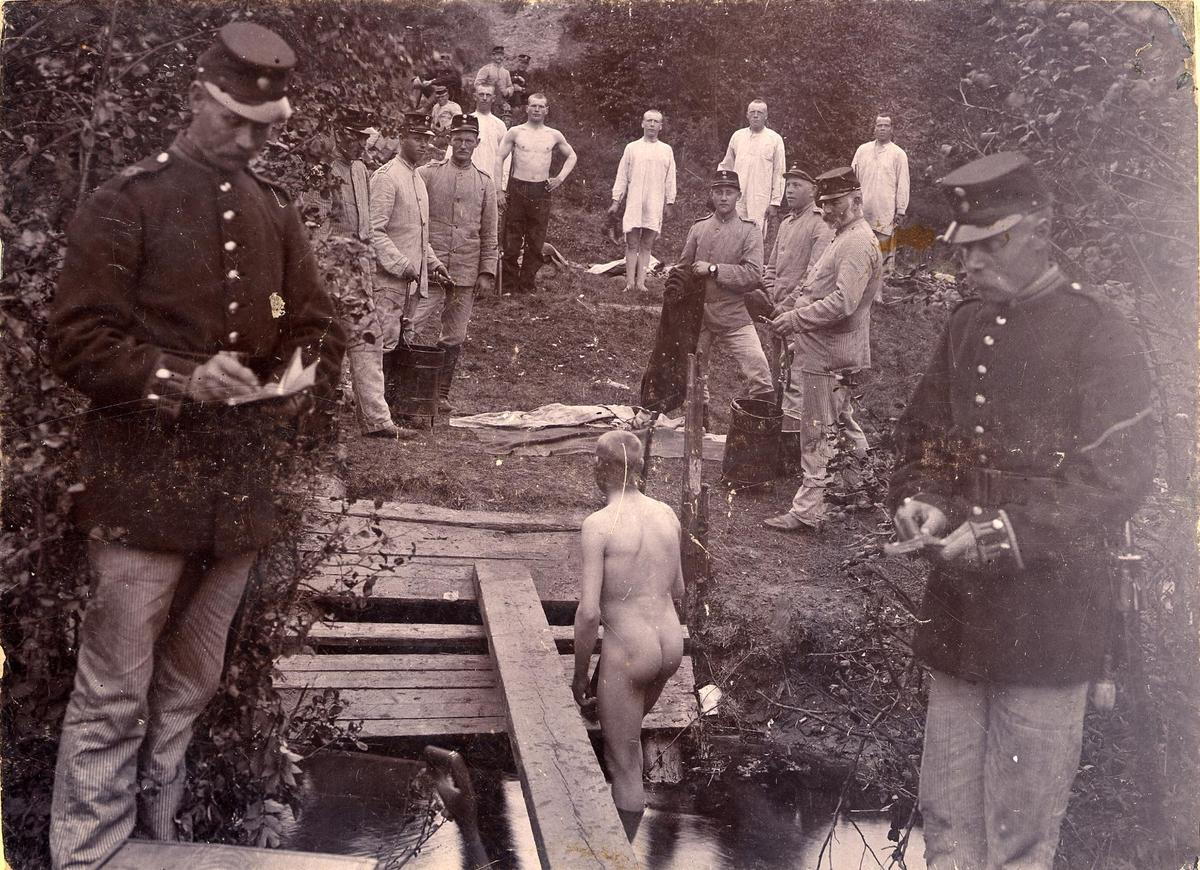 Soldat ur Älvsborgs regemente I 15, badar i vattendrag vid Fristadhed. Flera soldater väntar på sin tur. I förgrunden två officerare som antecnar i bok.