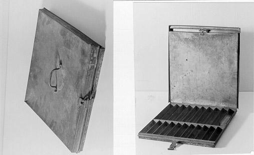 Frimärkslåda av järnplåt. Handtag på locket. Lådan tillslutesmed tudelat, vikbart överfall, som fästes i fastlödd nu bortfallenögla, genom vilken antagligen även hänglåsarm trätts. Locket upptarhalva höjden. Genom falsförsedd lucka, infällbar i locket, ochfastgörbar med vridbar järnten, beredes plats i locket förfrimärksark. Undre delen av lådan har fastlödd inredning med 10större och 11 mindre plåtrännor för frimärken.