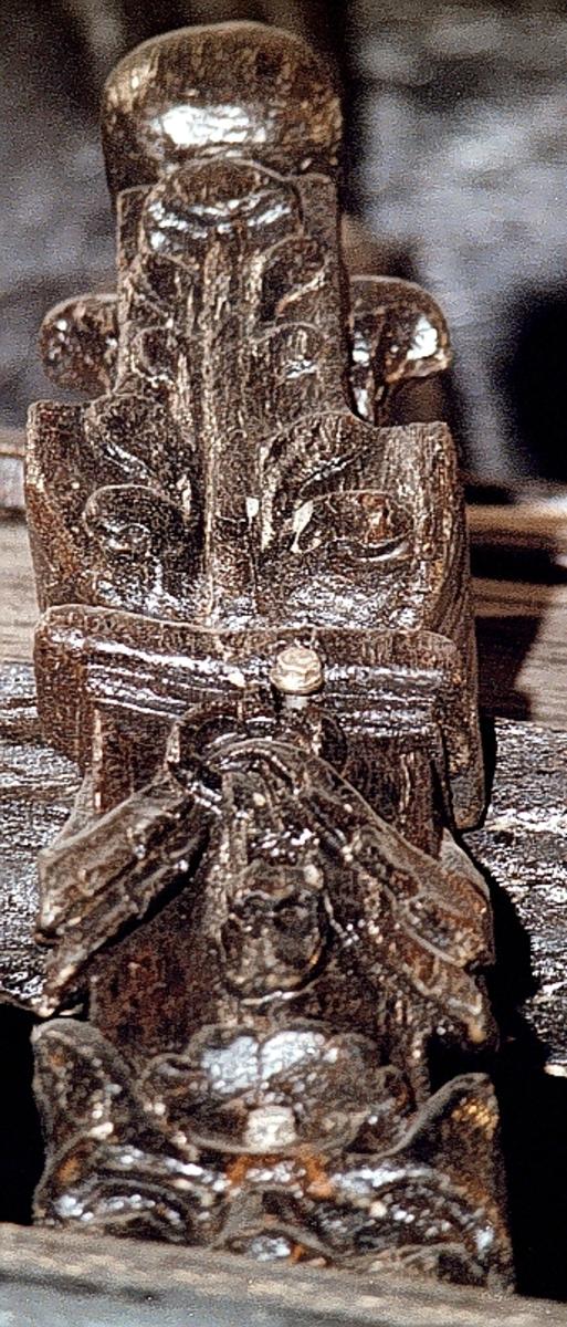 Ornament, upptill formad som en obelisk, krönt av ett stort klot. Obelisken vilar på en profilerad och snedställd platta som avgränsar den från en hög sockeln. Skulpturen är avplanad på baksidan med undantag för det krönande klotet som är rundskulpterat. Klotet är dock något planat på baksidan. Obelisken är skuren i ett stycke samt är rikt dekorerad med stora, långsträckta och mångflikiga blad, liknande eklöv, på framsidan och kortsidorna.  Nedtill är sockeln prydd med en enkelt skuren maskaron med långsmala ögon, bred klumpig näsa och grinande käft med små, spetsiga tänder. Sockelns övre del består av ett tjockt textilstycke, format likt en scarf, som trätts genom en stor ring. Dekorationen sträcker sig över kortsidorna. På baksidans nedre del finns en triangelformad fasning med tydliga huggspår. Skulpturen är mycket välbevarad.  Text in English: Ornament in the shape of an obelisk, topped with a large sphere and placed upon a high pedestal. A plinth seperates the obelisk from the pedestal. The sculpture is planed and flattened on the reverse except for the three-dimensional sphere. The obelisk is carved in one piece.  The obelisk is richly decorated with large, multi-lobed leaves similar to oak leaves, on the front and sides.  A grimacing mask with slit eyes, large nose and small pointed teeth decorates the pedestal. Above the mask a festoon of carved ribbon passes through a large ring. The festoon extends around the sides. The sculpture is very well preserved.