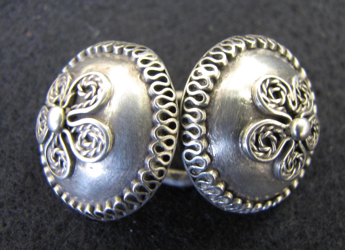 Ett par mycket vackert arbetade länkknappar av silver, ihåliga och märkta: SLB (otydligt).  Från Stola, Orust, Bohuslän. Endast ett par är stämplade.  Silversmeden Sven Lars Ljungberg föddes 1754 som son till silversmeden i Örebro Nils Ljungberg (1714-1788). Han stämplade arbeten i Örebro från 1786 till sin död 1819.