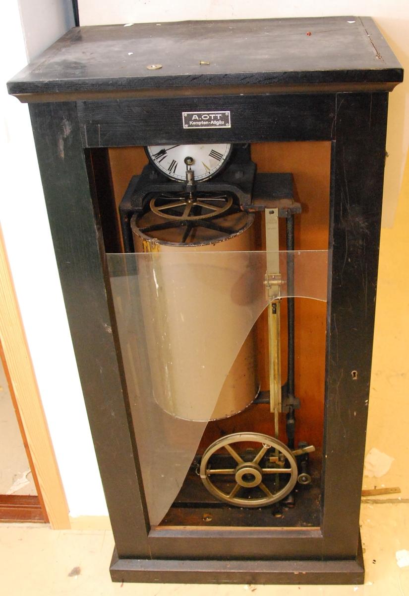 """Teknikk: Mekanisk, vertikale stag som beveges ved tannhjul, og med """"blyant""""-holder for avtegning av vannstandsendringer på vertikal sylinder som drives av et urverk."""