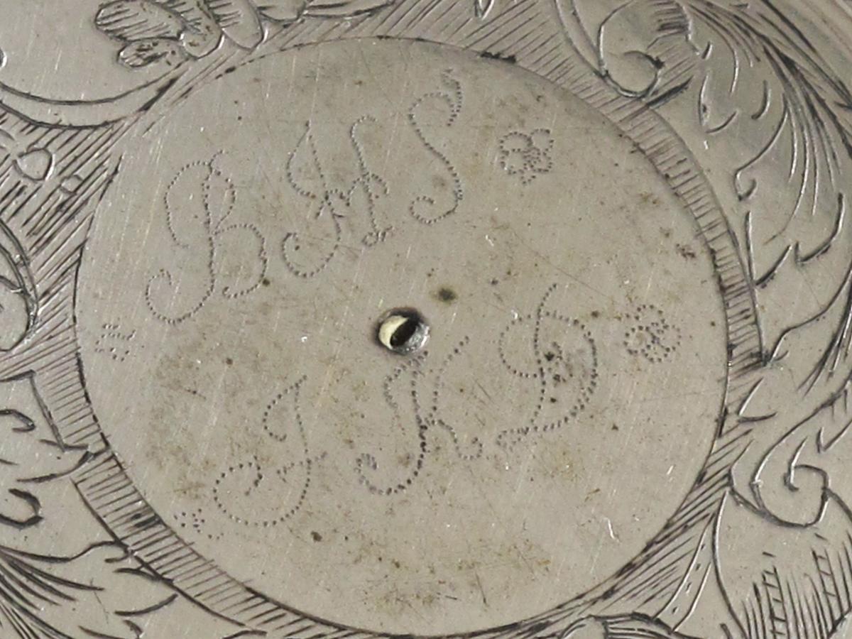 Stentøykrus m. lokk av sølv.  Flatt lokk, buet kant m. rette knekk, sirkelrundt oppdrevet  midtfeldt m. akantusgravyr samt bånd og skjellignende ornament,  i sirkel innenfor innprikket  BHS  JKD,  lokkgrep som hode på stående blad m. opprullede fliker, støttet på forsiden m. to  buede sølvtråder, den ene mangler. Stpl.   LB  i hjerte.   Lokket montert på sylindrisk stentøykrus, nederst  brunt, riflet feldt, så glatt, derpå lyst, riflet  feldt, profilert. Buet hank.    Tilst mai 1961: God, lokket litt løst festet.
