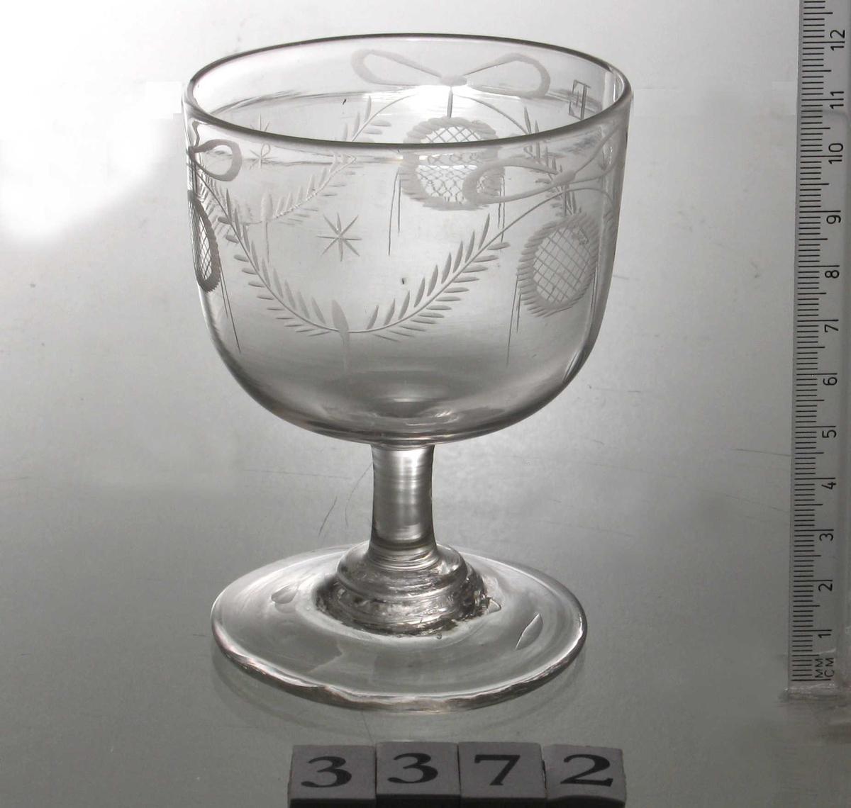 Vinglass, laget i  England ca. 1820.  Krystall.  Klokken sylinderformet, lav, slank stett,  og med tilnærmet sirkelrund fot.   Gravert mønster  på  klokken i form av guirlandere.  Øverst på kanten bokstavene   NE  (Niels Eldrup)   inngravert. Blåsemerket tydelig  under foten, noen bobler i godset samme  sted. Noen ujevnheter også på klokken.  Tilst. juli 1963: God.