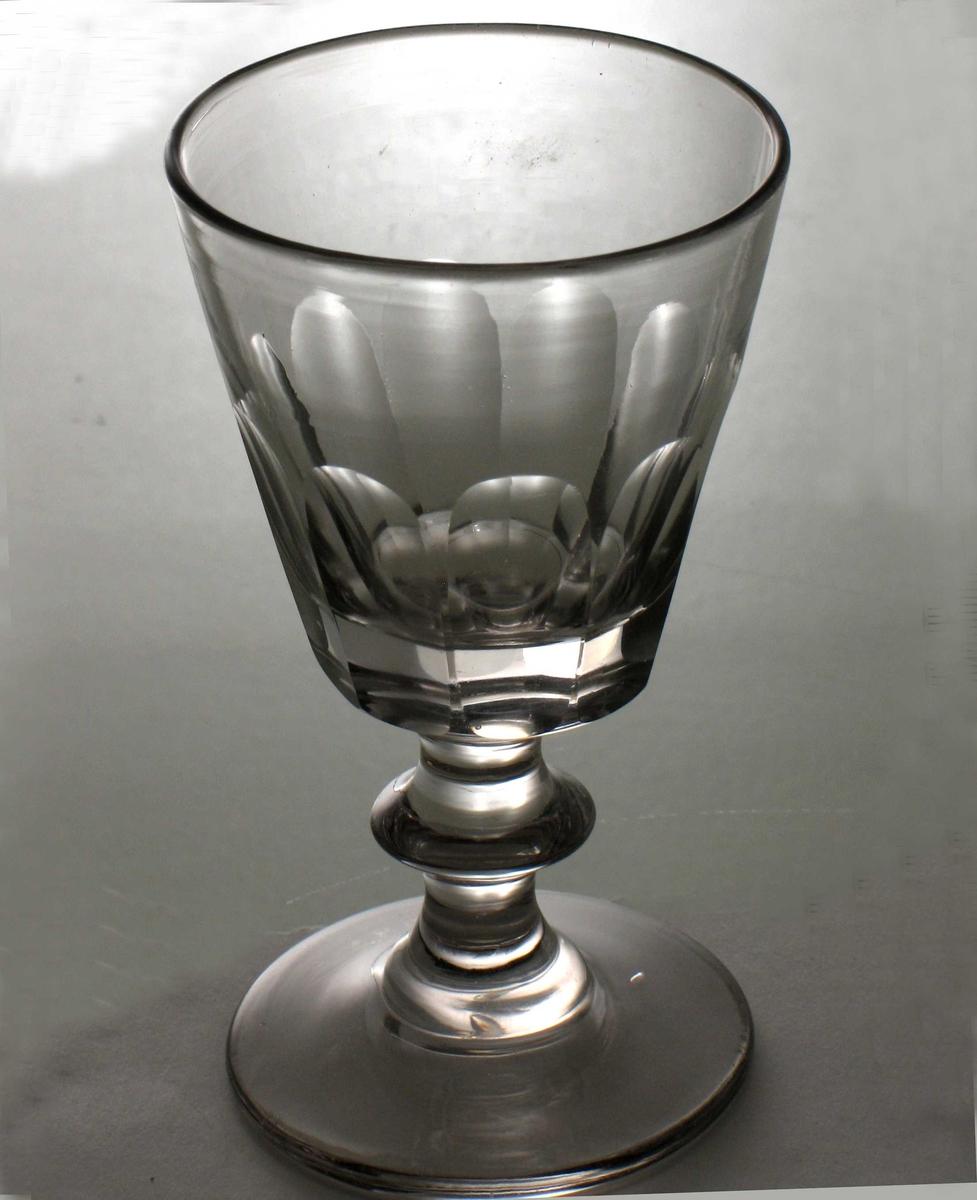 Rund glatt fot. Balusterstett med bare en vulst, klokke med  rett  bunn, oppoverskrånende sider,   fasettslepet  nedre halvdel. Forholdsvis tykt glass. Som AAM.4439,men st re.