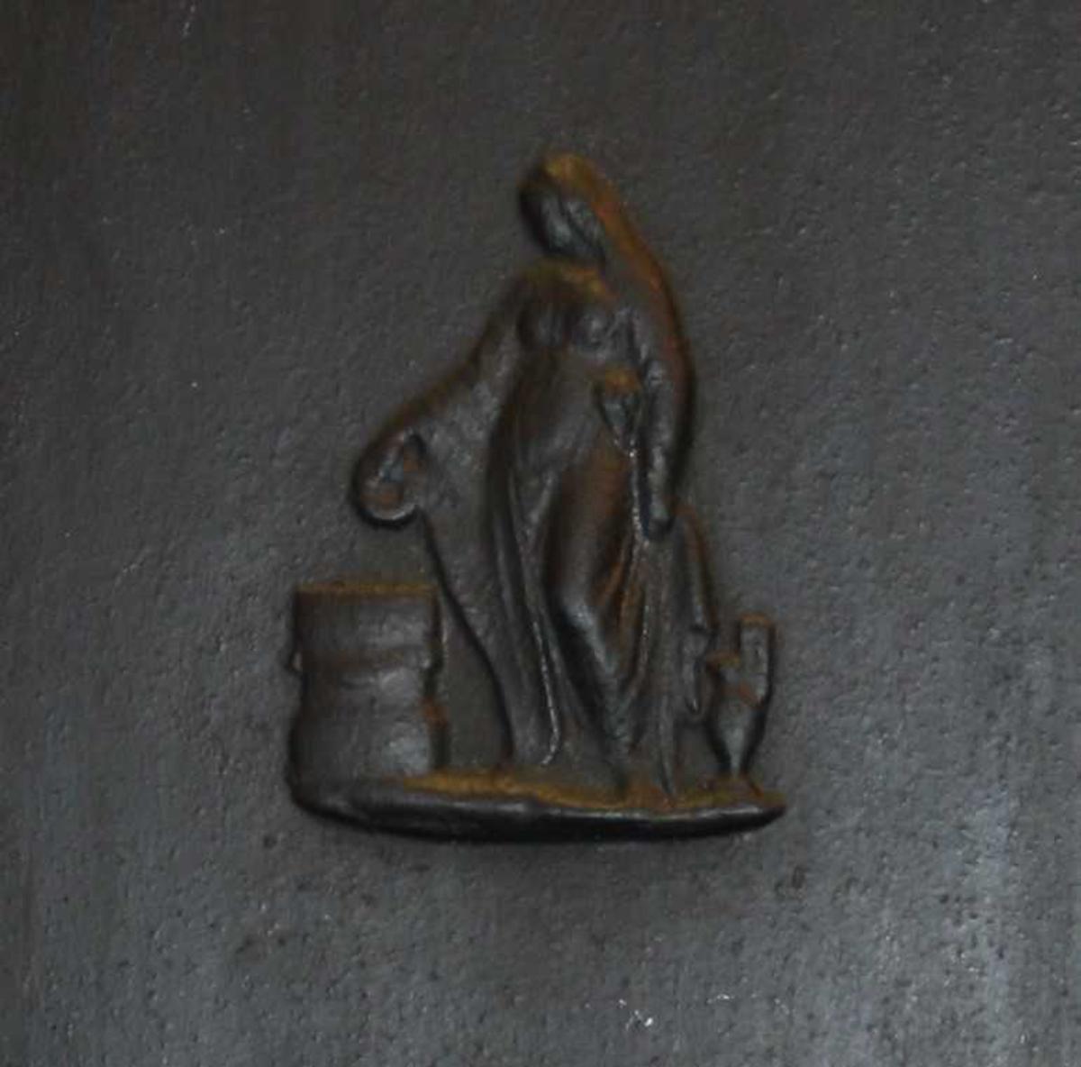 Kvinnefigur i relieff.