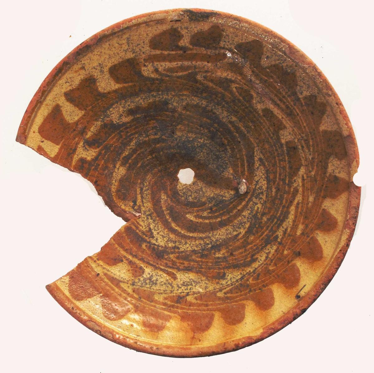 Leirtøy, rødbrunt, litt lyst gods, gul og okerbrun  glasur.  Lav stett med markert bunnring, glasert også under bunnen, skrå sider med en rundet brem. Innvendig gull bunnfarge med en tett okerbrun ranke i spiral fra midten og helt ut i kanten.   Tilstand: et V-formet skår i kanten og et lite hull midt i bunnen.