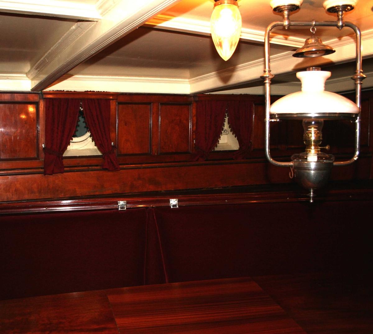 Salong, 1. klasse, fra skipets akterende,  med mahognypanel, mahognybord, sofaer trukket med rød plysj,  rød mønstret teppe på gulvet.  Med bufé, speil og skipsklokke .